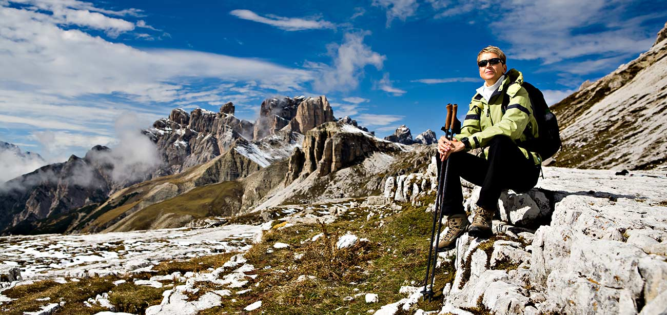 Woman sitting on rocks with Dolomites and blue sky with white clouds on the background