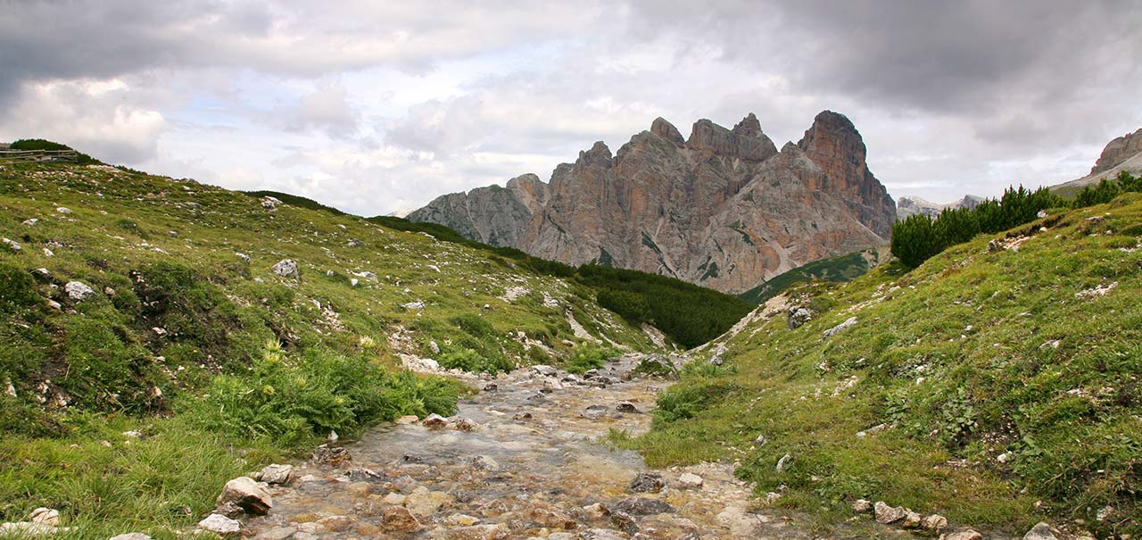 Stream flowing in the middle of a green meadow with Dolomites and grey clouds on the background