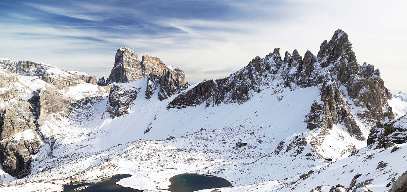 Panoramic view of the snowy Sella Group with blue sky and white clouds