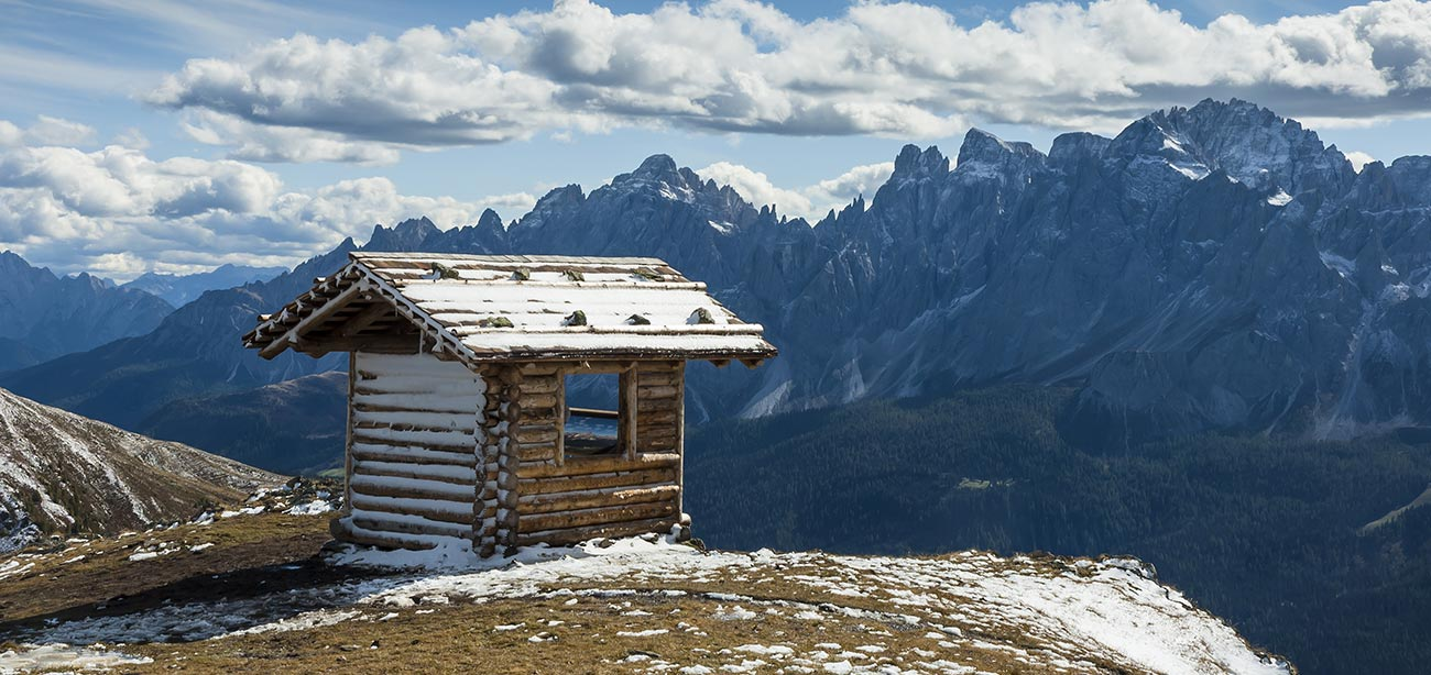 Small snowy wood house above mountain with Dolomites on the background