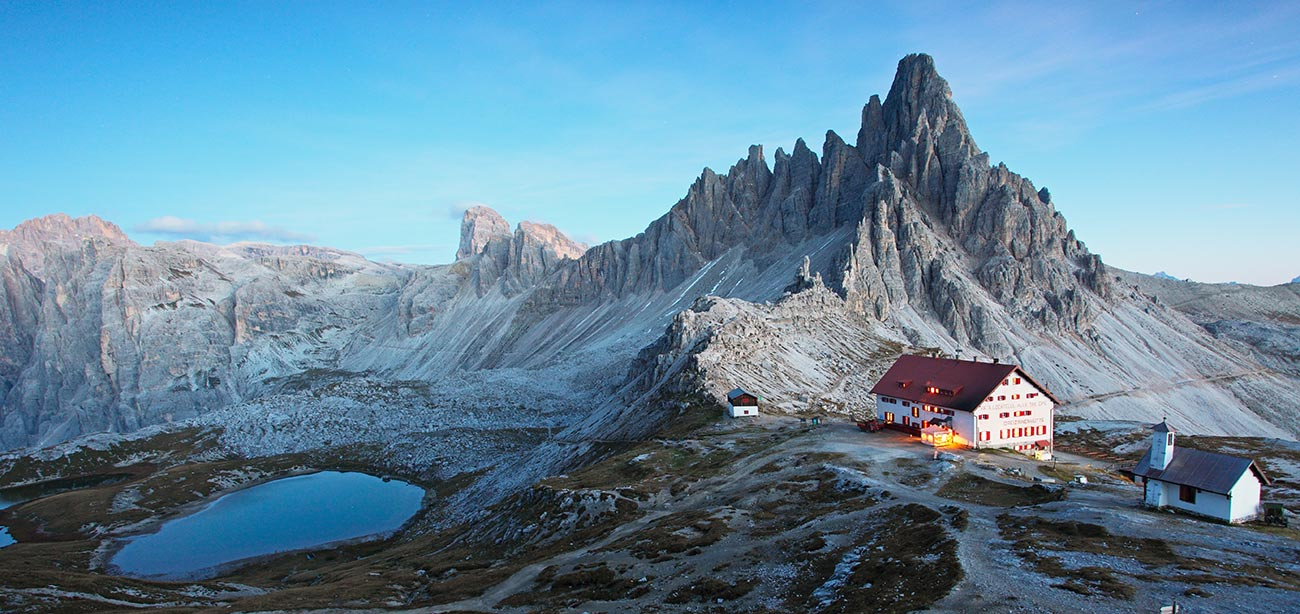 Rifugio Locatelli near alpine lake with Dolomites peak on the background and blue sky