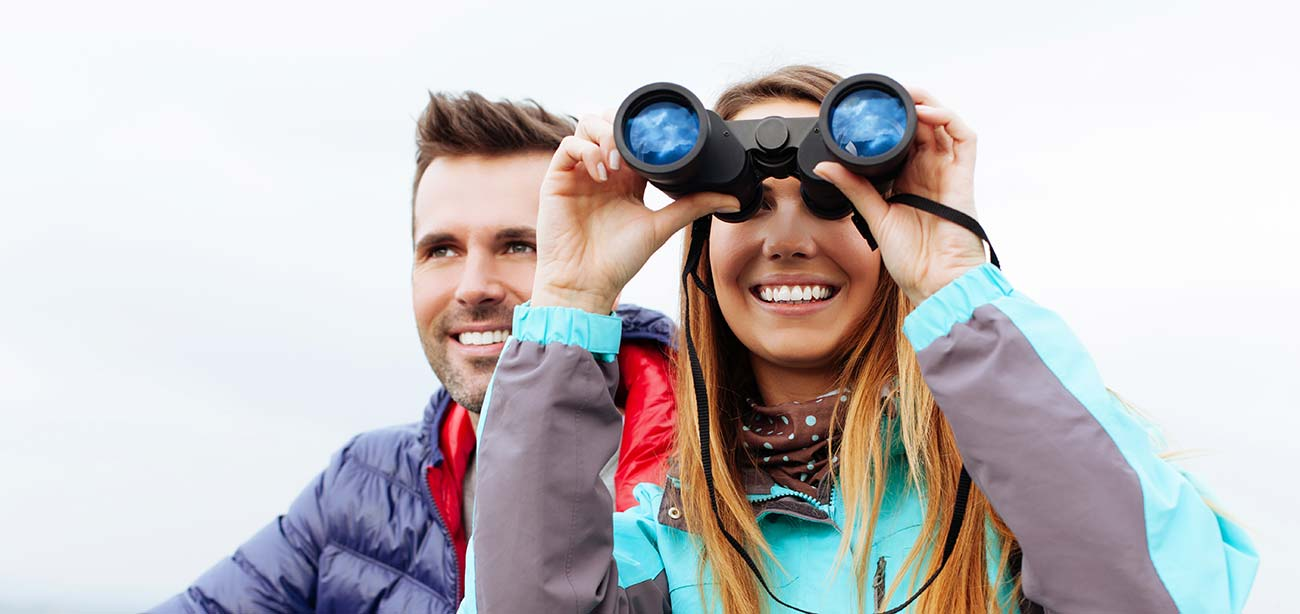 Girl with binoculars near smiling boy with grey background