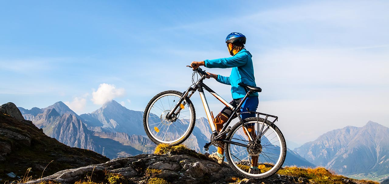Person with mountain bike standing in front of panoramic view of mountains and blue sky