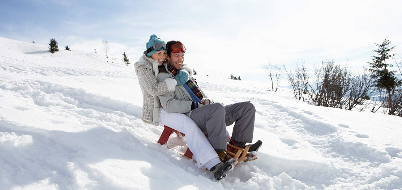 A man and a woman down on the fresh snow with the sled