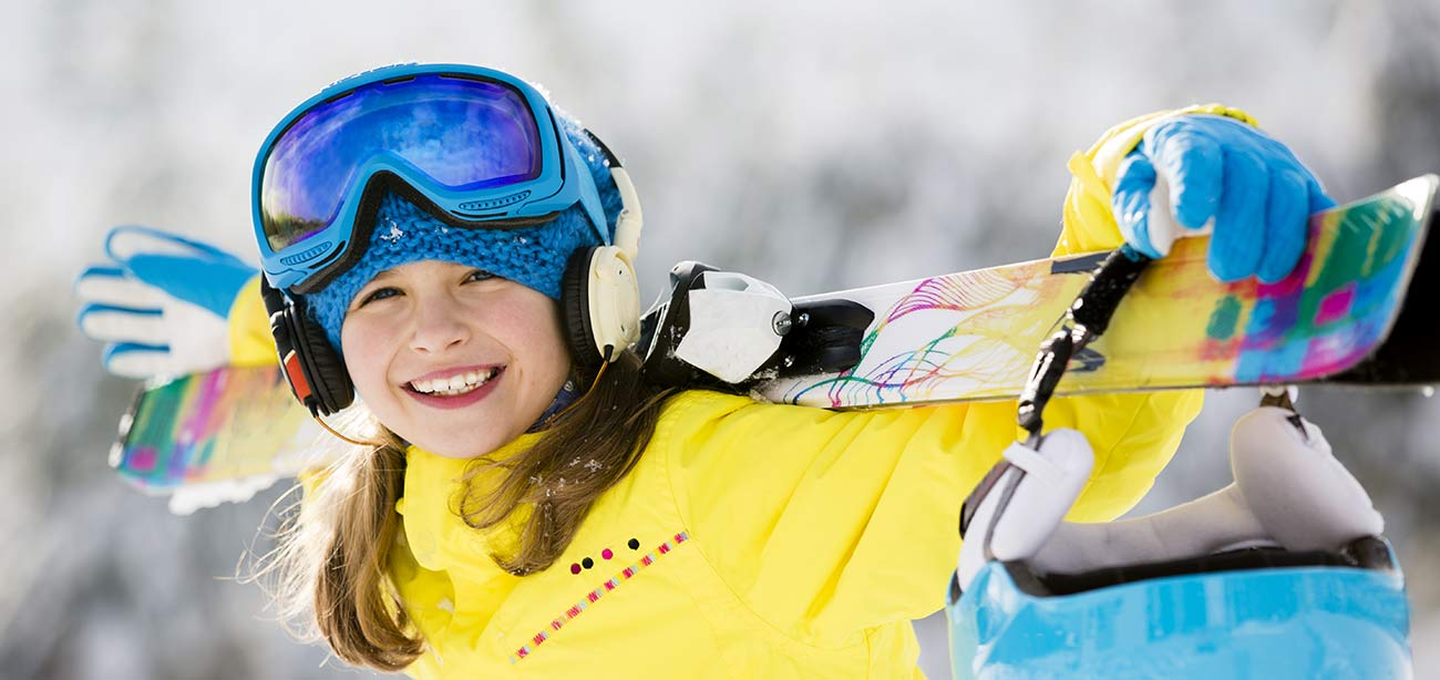 Girls with yellow jacket holds skis behind the head