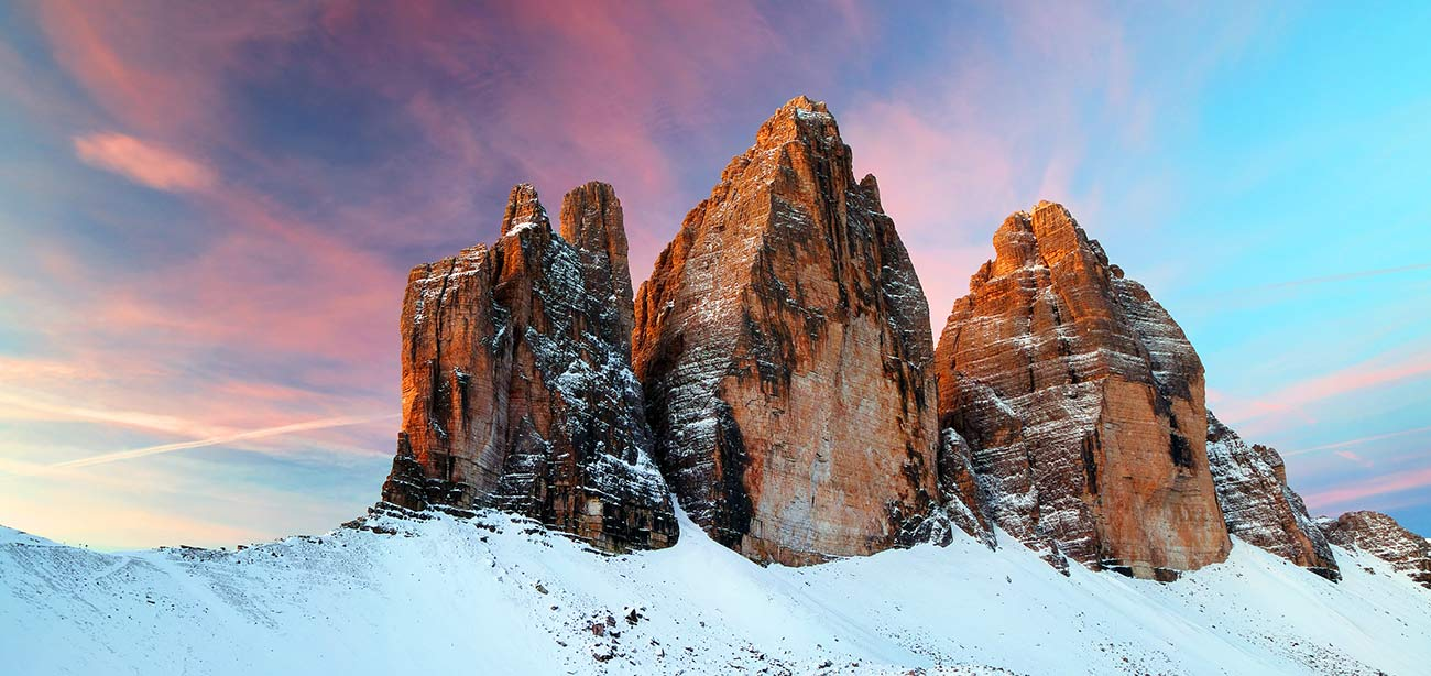 The Three Peaks lavaredo covered with snow at sunset