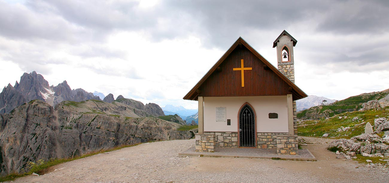 Small church on earth clearing with Dolomites and clouds on the background