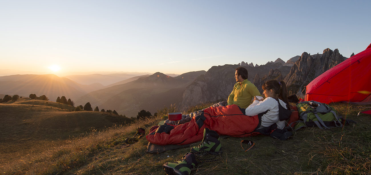 Couple with tent and sleeping bag watching twilight on the horizon with Dolomites on the background