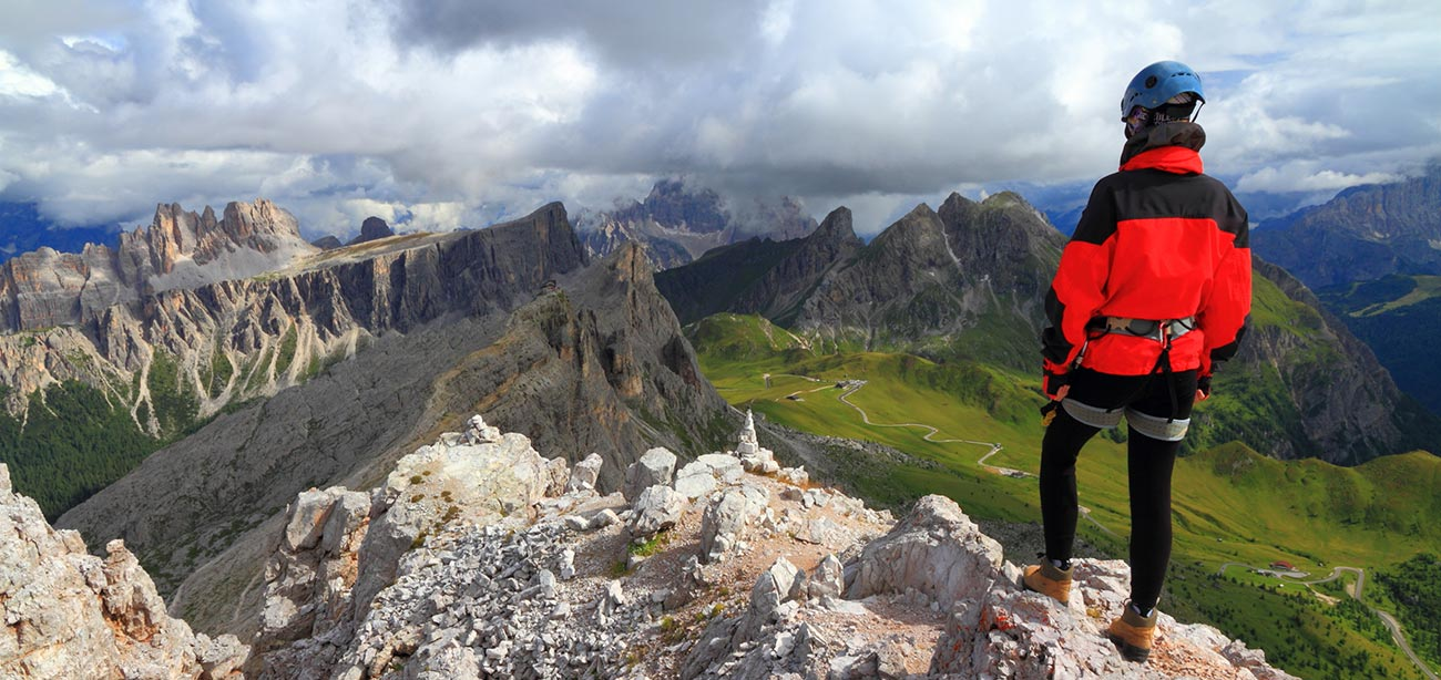 Mountaineer from behind standing on a peak watching Dolomites and clouds on the background