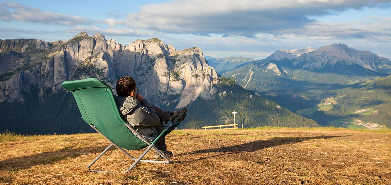Man sitting on deckchair enjoying the panoramic view of the Dolomites on the background