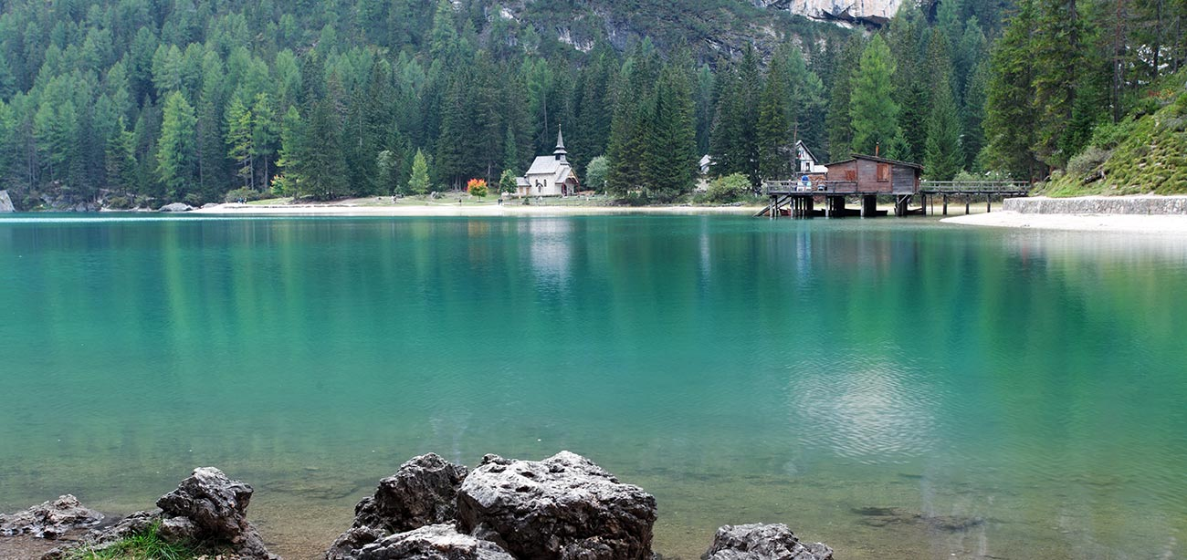 Braies lake with pier and woods on the background
