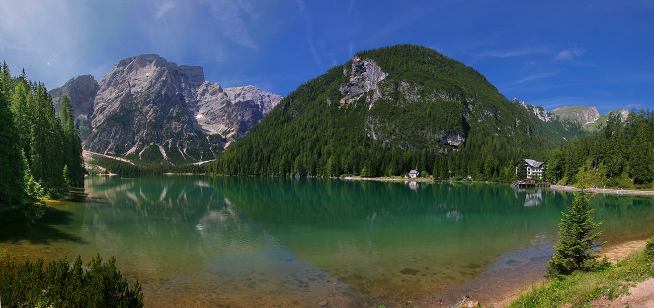 Panoramic view of Braies lake with green mountains and blue sky on the background