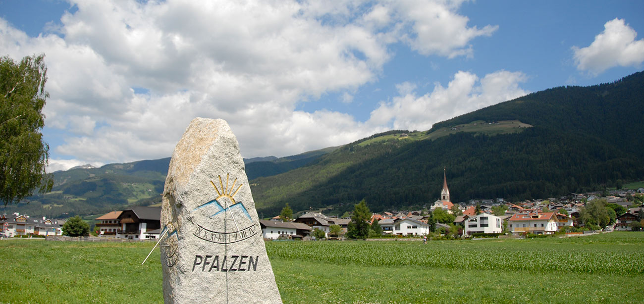 Stone with Falzes written on with village, green mountains and sky on the background
