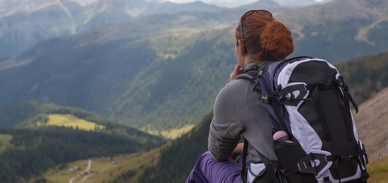 Woman with backpack sitting from the back watches panoramic view of the green valley