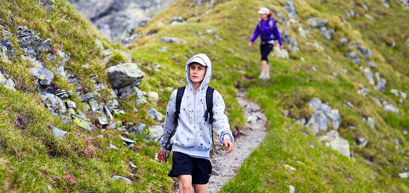 Persons with backpacks walking on small path with green meadows and rocks
