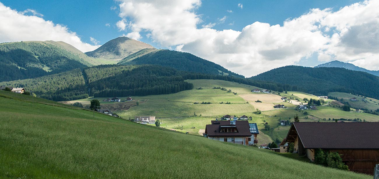 Alpine houses on green hill with mountains and green fields and sky on the background