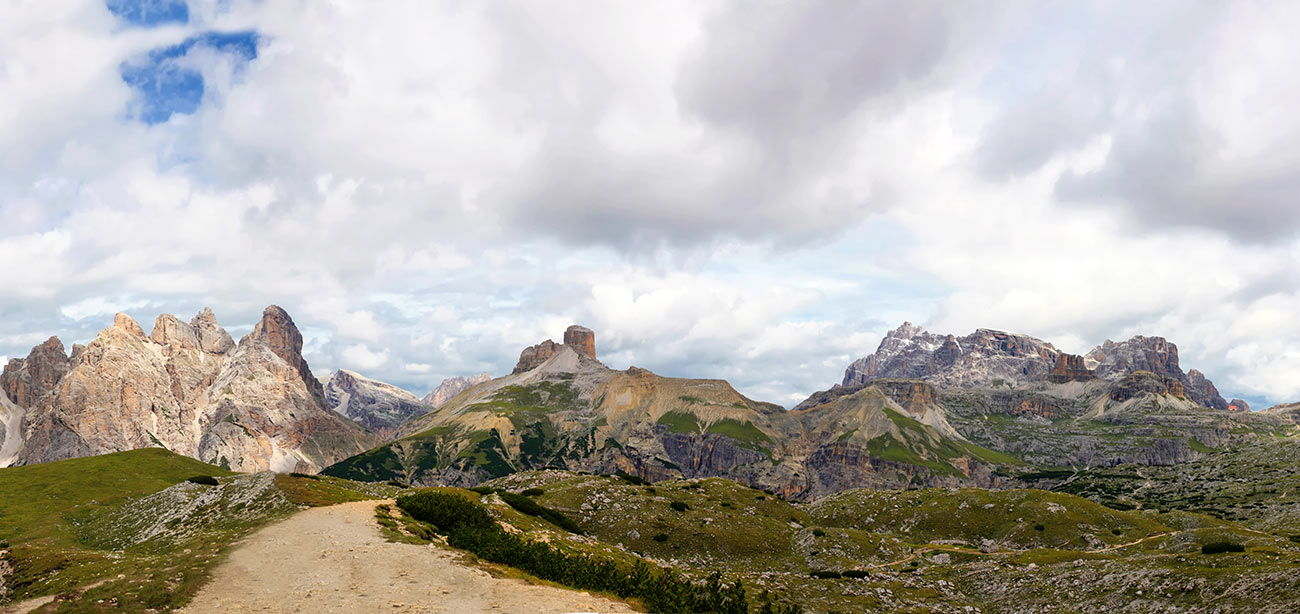 Rocky path with Dolomites and white and grey clouds on the background