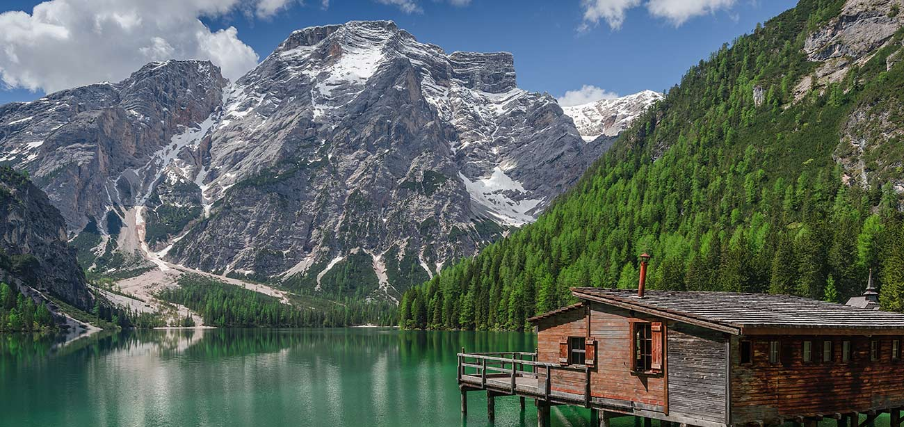 Small wood house on the shore of Braies lake with Dolomites on the background