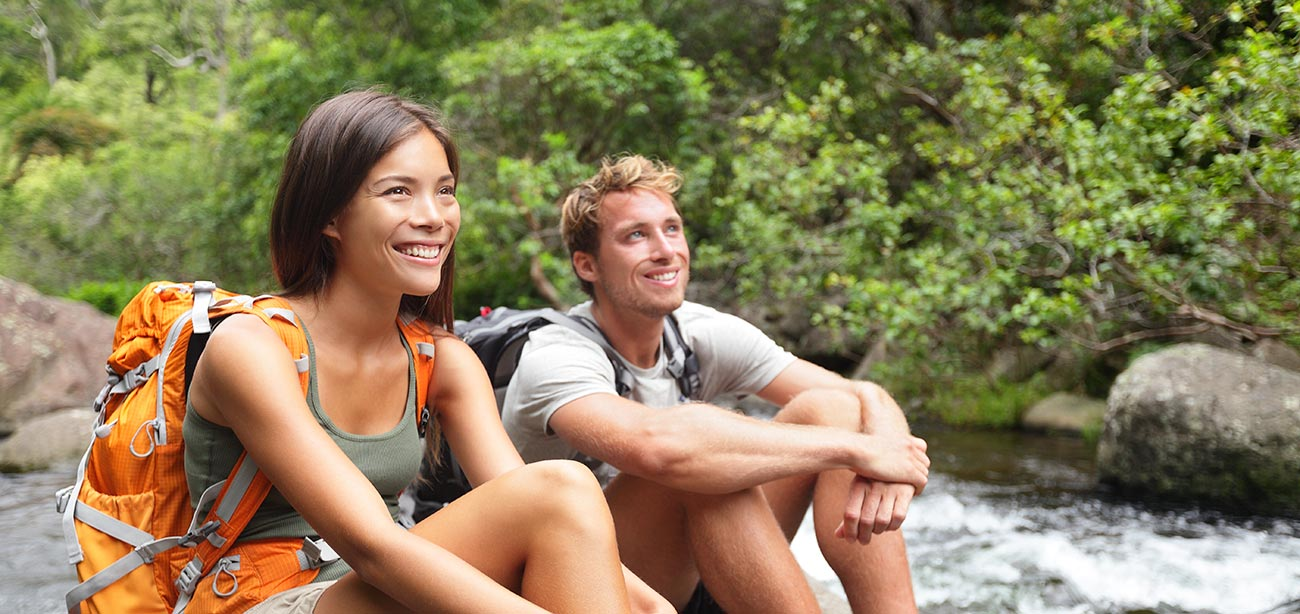 Smiling couple with backpacks sitting near a stream in the middle of woods