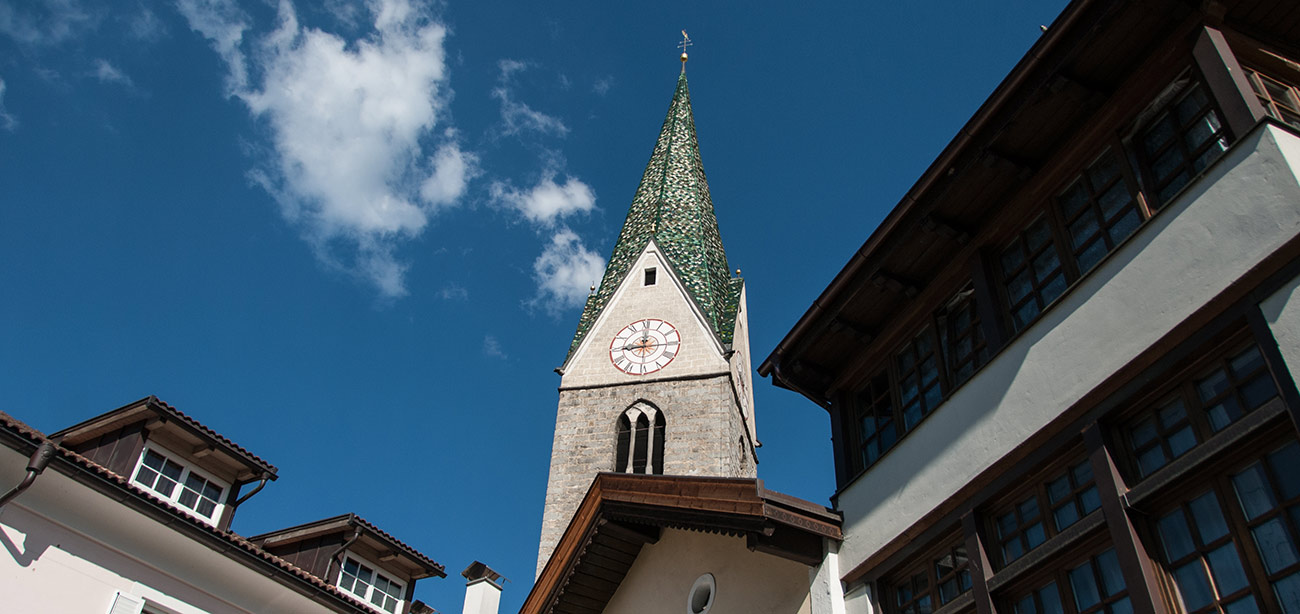 The green bell tower of Rio di Pusteria standing out on blue sky
