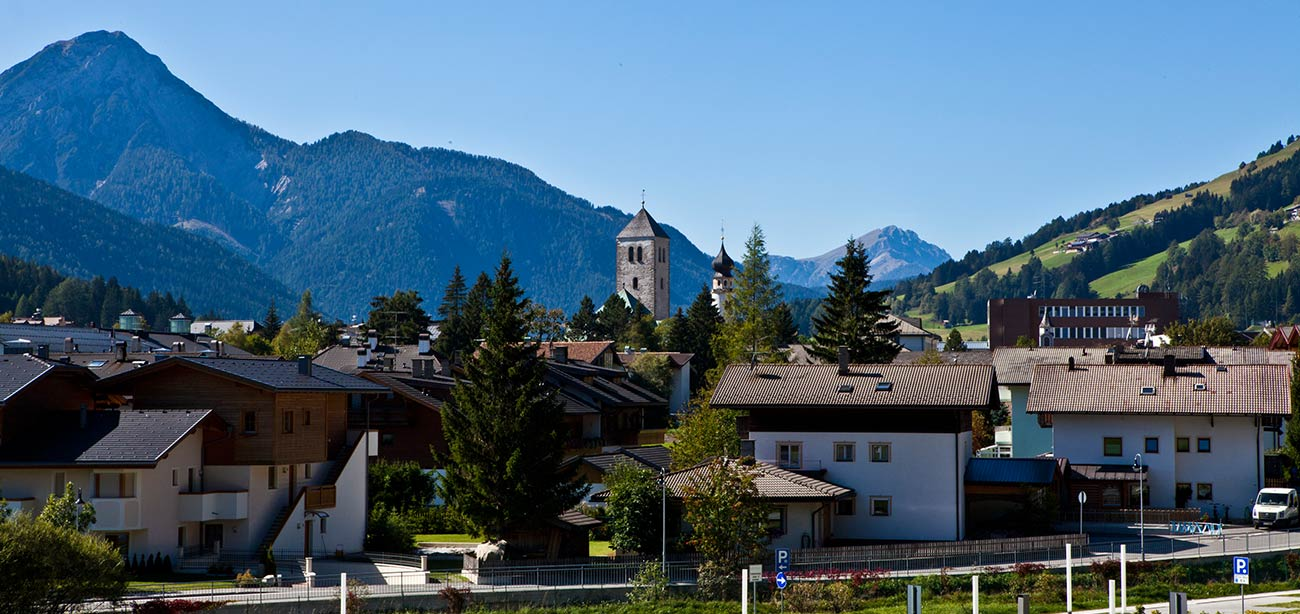 Village of San Candido with mountains covered by woods and blue sky on the background