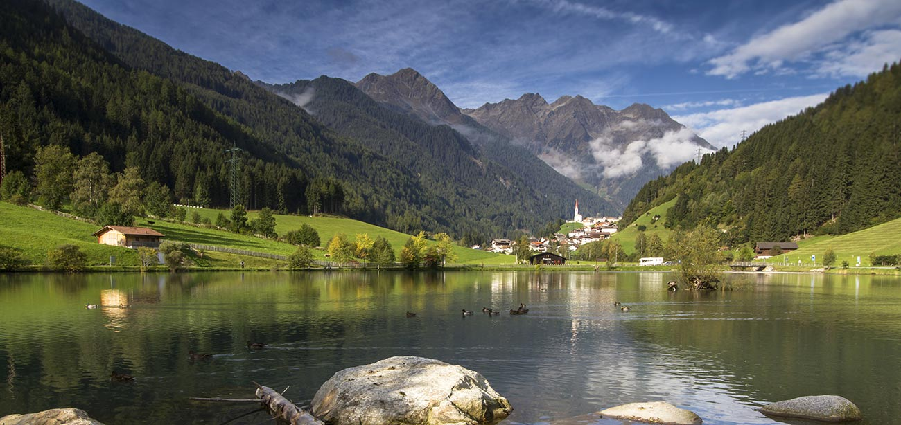 Mountain lake with village of Selva dei Molini and mountains on the background
