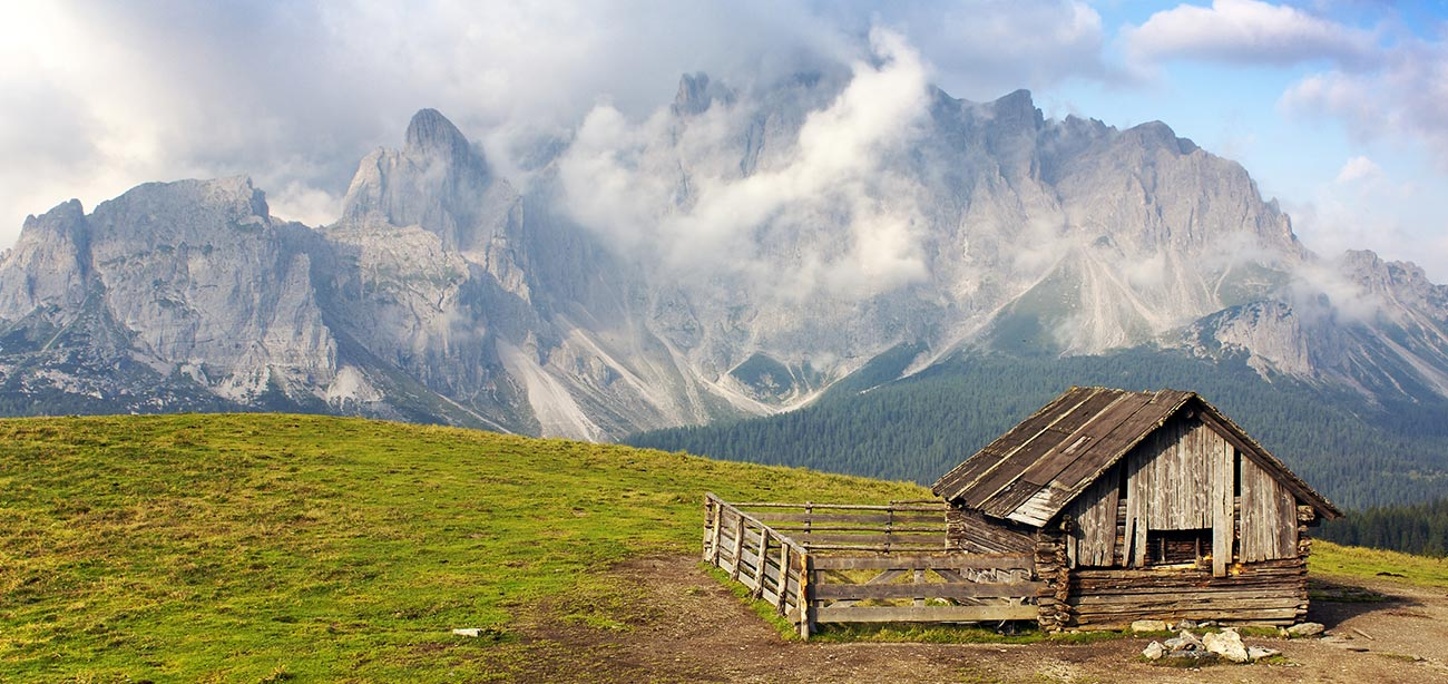 Small wood house on green meadow with Sesto's Dolomites on the background