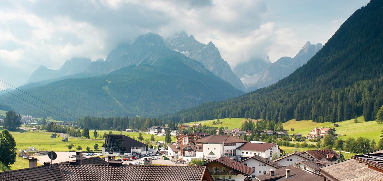 Panoramic view of the roofs of the village of Sesto with Dolomites on the background
