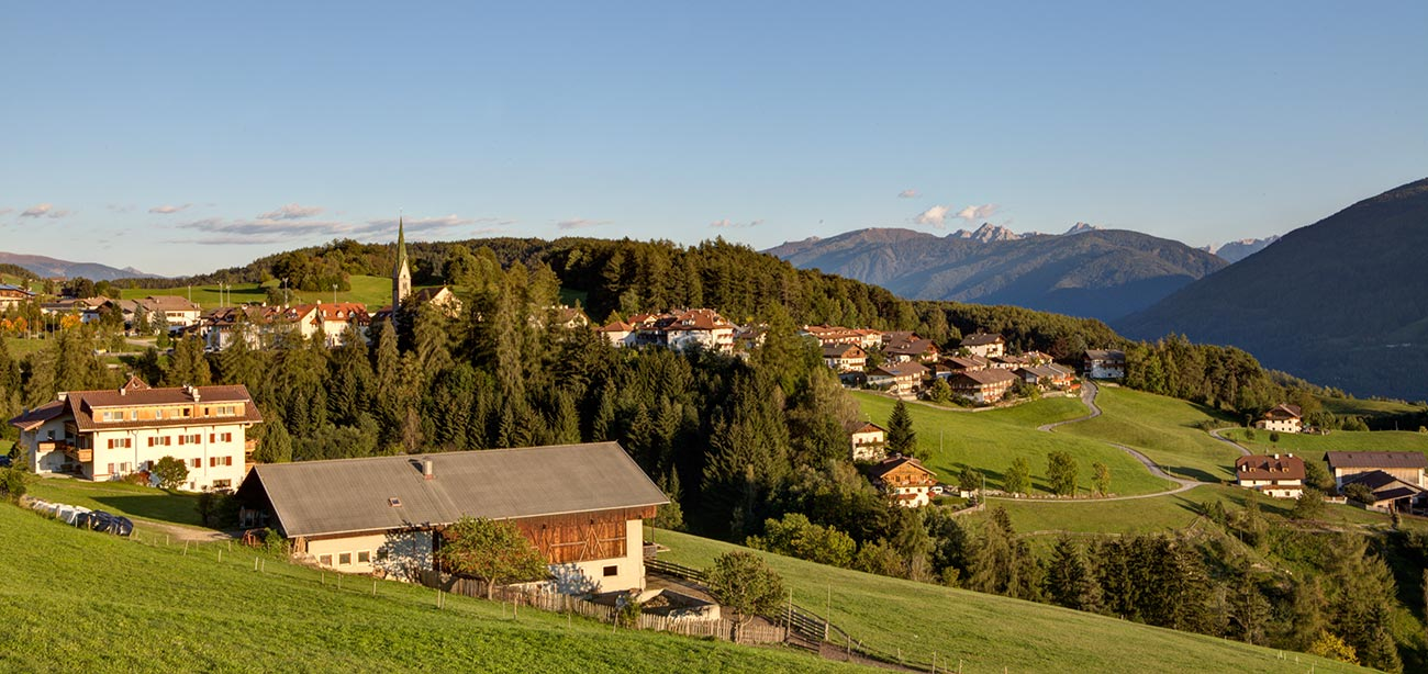 View of the village of Terento in the middle of woods and meadows with blue sky on the background