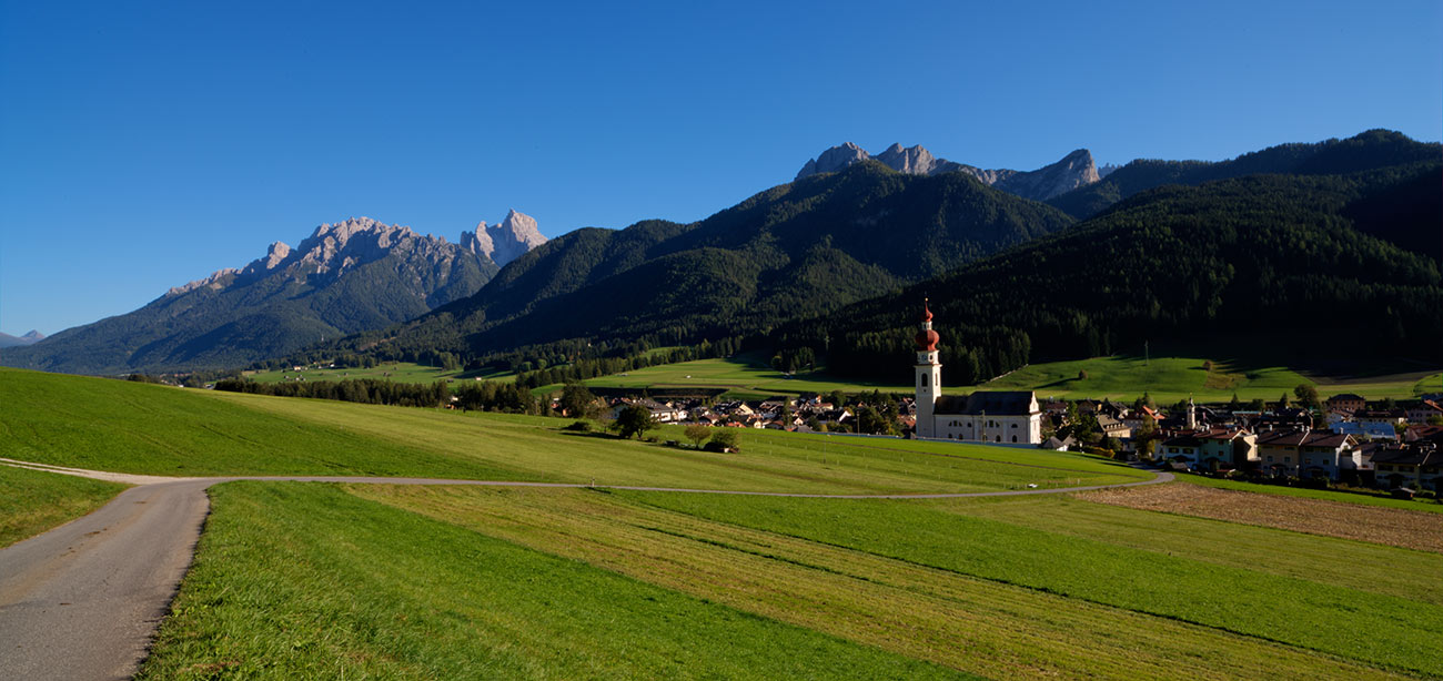 Green field with village of Valdaora and Alps on the background